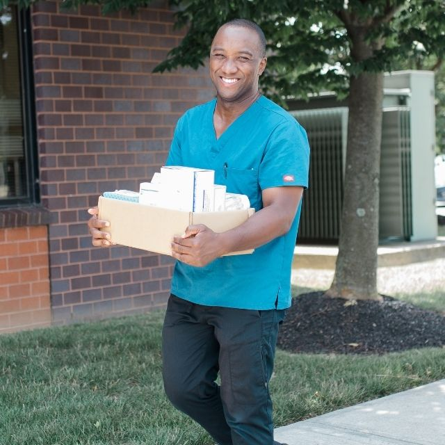 Mobile Phlebotomist carrying paperwork to medical office
